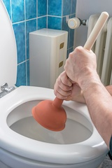 A plumber using a plunger to unblock a household toilet