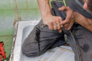 Plumber cleaning hair from drain in bathroom